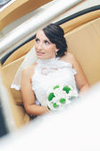 Bride in a vintage car with white dress and green bouquet — Stock Photo