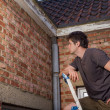 Young man inspecting the wall of an old house — Stock Photo