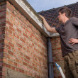 Stock Photo: Young man inspecting the roof of an old house