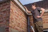 Young man inspecting the roof of an old house — Stockfoto