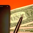 Cell phone, banknotes and pen — Stock Photo #22087957