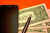 Cell phone, banknotes and pen — Stock Photo