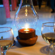 Candle in lamp and wine glasses on table — Stock Photo #25639383