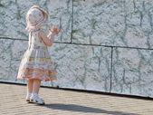 Het kleine meisje in een jurk en een hoed — Stockfoto