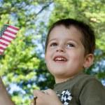 Cute little boy waving an American flag — Stock Photo