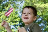 Söt liten pojke viftade en amerikansk flagga — Stockfoto