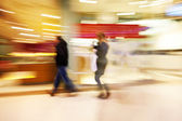A shopper walking against shop window — Stock Photo