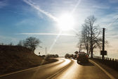 Cars driving down country road — Stock Photo