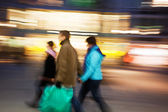 Couple with shopping bags walking past at dusk — Stock Photo