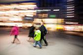 Family walking down shopping street at dusk — Stock Photo