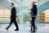 People Walking Quickly down Hall in Office Building — Stock Photo