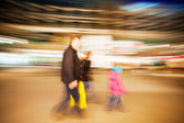 Family walking past window display in clothes shop at dusk — Stock Photo