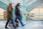Two Blurred Commuters Walking Along Modern Corridor in Motion Bl — Stock Photo