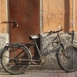 Abandoned old rusty bicycle leaning against a wall — Stock Photo