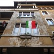 Italian flag waving on decadent home - Stock Photo