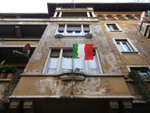 Italian flag waving on decadent home — Stock Photo