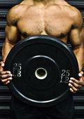 Athlete holding weight — Stock Photo