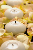 Candle and rose petals on mat — Stock Photo
