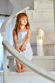 Little red-haired girl on the stairs — Stock Photo
