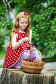 Girl in with a basket of cherries — Stock Photo