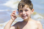 Boy with shell in hand on the beach — Stock Photo