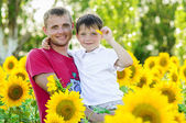 Father and boy in a sunflowers field — Stock Photo