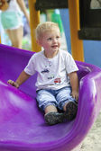 Little boy on a children's slide in the park — Stock Photo