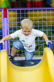 Little boy on a children's slide in the park — Stock Photo