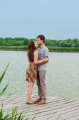 Young girl and the young man on the dock by the river — Stock Photo