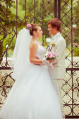 Beautiful bride and groom smiling at each other — Stock Photo