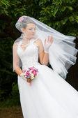 Belle mariée dans une robe blanche avec un bouquet à la main — Photo