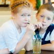 Boy and girl drinking a drink with ice through a straw — Stock Photo