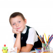 Little boy at his desk with an album for drawing, pencils and books on white background — Stock Photo #30818041