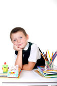 Little boy at his desk with an album for drawing, pencils and books on white background — Stock Photo