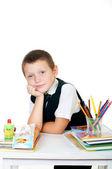 маленький мальчик на своем столе с альбомом для рисования, карандаши и книги на белом фоне — Стоковое фото