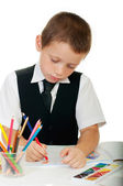 The boy draws pencils in an album on a white background — Stock Photo