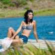 Young beautiful girl on the pier at the river in denim shorts — Stockfoto