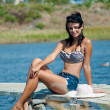 Young beautiful girl on the pier at the river in denim shorts — ストック写真