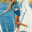Young beautiful girl on the pier at the river in denim shorts — Stock Photo