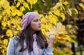 Young girl in a park in autumn with yellow leaves — Stock Photo
