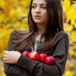 Young girl in autumn park with apples — Stock Photo
