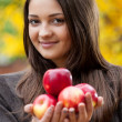 Young girl in autumn park with apples — Stock fotografie
