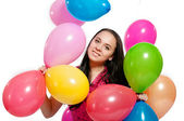 Young girl with bright colored balloons on a white background — Photo