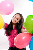 Young girl with bright colored balloons on a white background — Stock fotografie