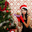 Beautiful girl near a christmas tree with gifts in hand — Stock Photo