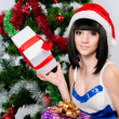 Beautiful girl in santa hat near a christmas tree — Stock Photo