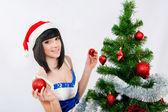 Beautiful girl in santa hat near a christmas tree — Stock Photo