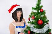 Beautiful girl near a christmas tree — Stock Photo