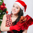 Beautiful girl  near a christmas tree with gifts — Photo