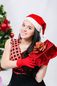Beautiful girl near a christmas tree with gifts — Stok fotoğraf